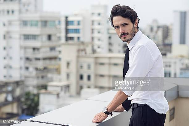 handsome man standing on the balcony