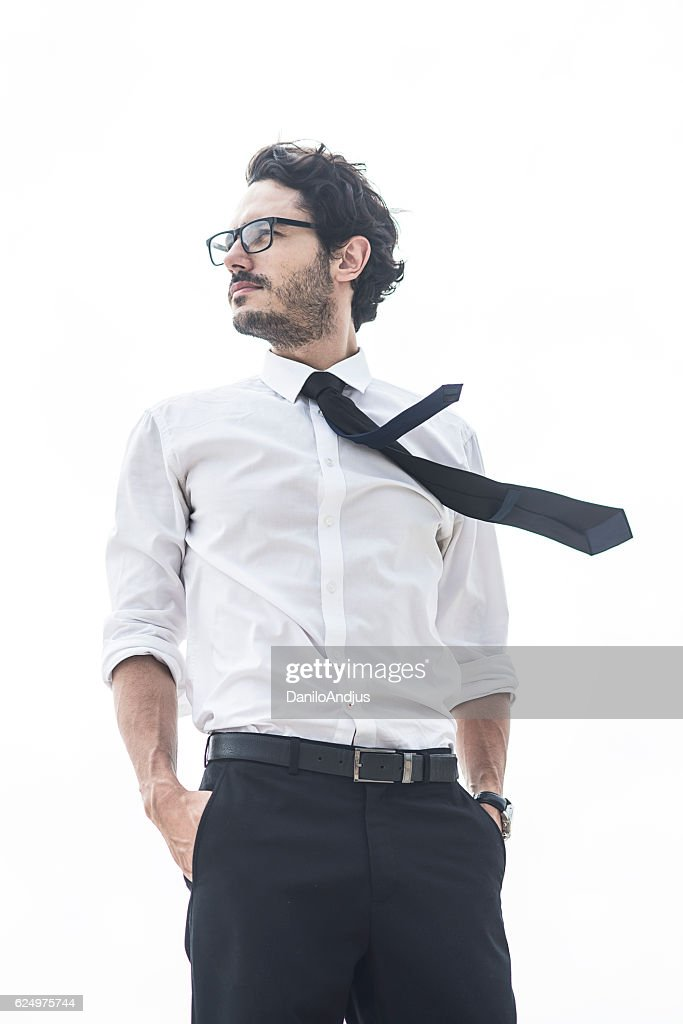 handsome man standing with his hands in pockets : Stock Photo