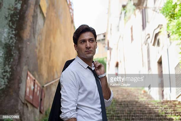 handsome man strolling along the streets of rome - jeté sur l'épaule photos et images de collection