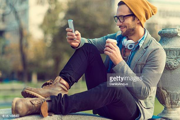 handsome man taking a break and using his smartphone