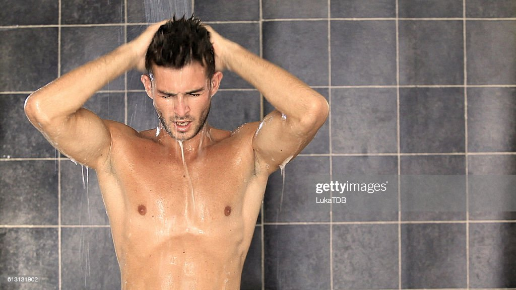 Handsome man taking a shower and enjoying it : Stock Photo