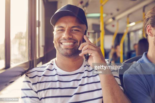 handsome man talking on smart phone in public bus - izusek stock pictures, royalty-free photos & images