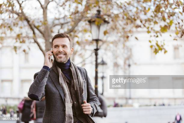 handsome man talking on smart phone outdoors in the city - izusek stock pictures, royalty-free photos & images