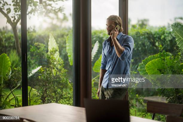 handsome man talking on smartphone in contemporary design house - premium access stock pictures, royalty-free photos & images