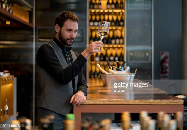 handsome man tasting wine at a wine store looking very focused - bar drink establishment stock photos and pictures
