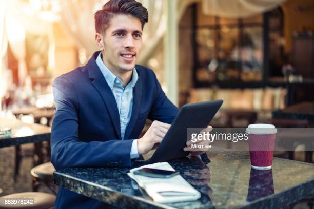 Handsome man texting on his tablet
