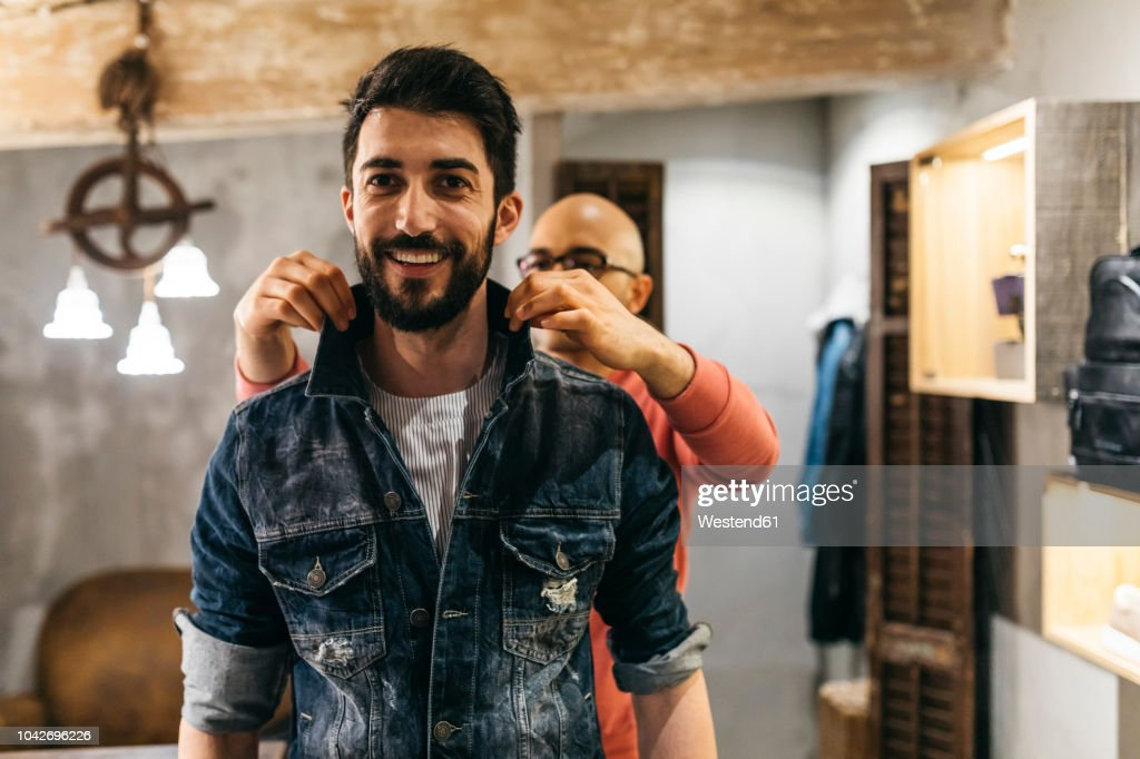 Handsome man trying on new denim jacket with stylist in modern boutique : Stock Photo