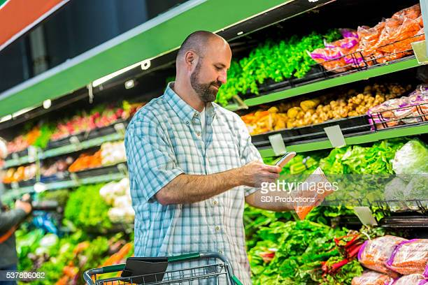 Handsome man uses phone at grocery store