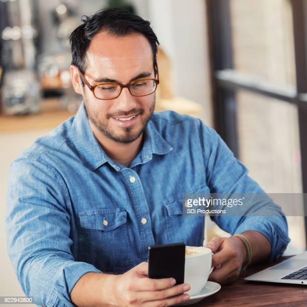 Handsome man uses smart phone while in coffee shop
