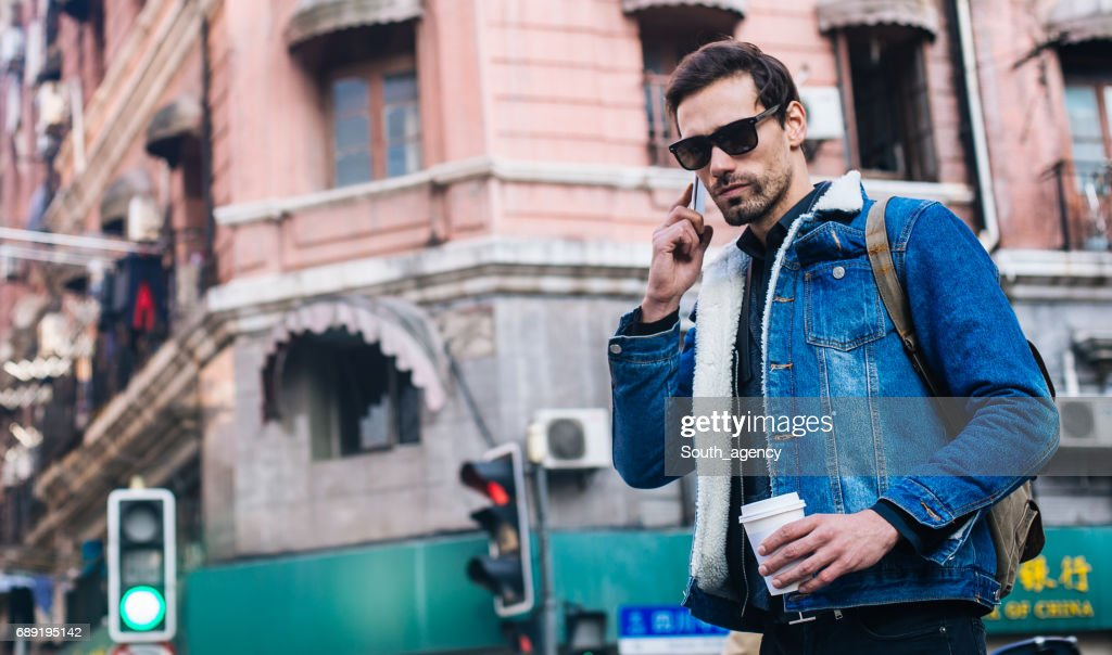 Handsome man using a phone on the coffee brake : Stock Photo