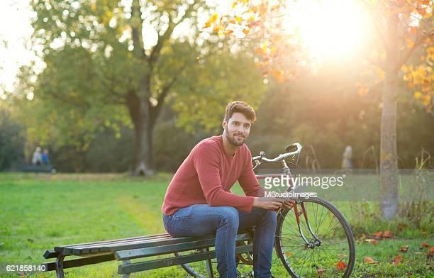 Handsome man using digital tablet at the park.
