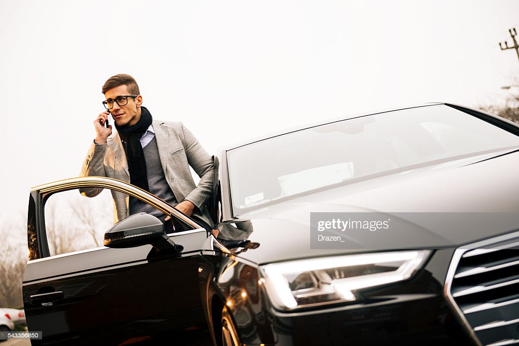 Handsome man using iPhone 6+ and driving new Audi A4 : Stock Photo