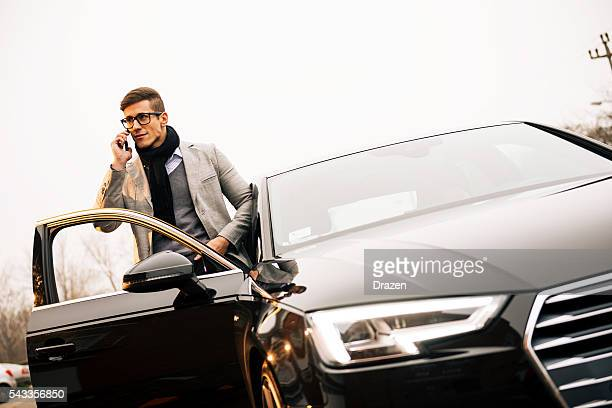 handsome man using iphone 6+ and driving new audi a4 - audi a4 stock photos and pictures