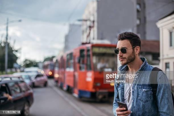 hombre guapo con teléfono móvil en la calle - un solo hombre joven fotografías e imágenes de stock