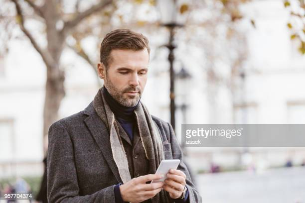 handsome man using mobile phone outdoors in the city - tweed stock pictures, royalty-free photos & images