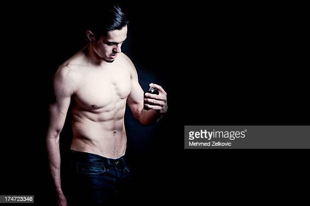 Handsome man using perfume