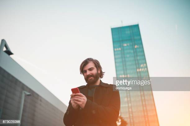 Handsome man using phone in the city street