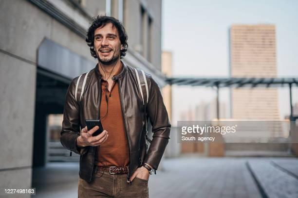 guapo hombre usando el teléfono en la calle del centro - masculinidad moderna fotografías e imágenes de stock