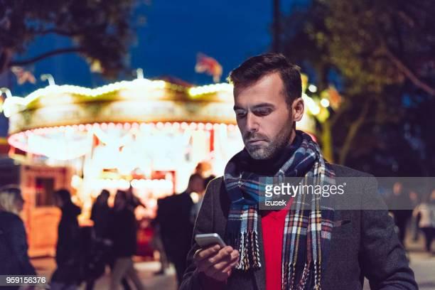 gut aussehender mann mit smartphone vor beleuchteten karussell - izusek stock-fotos und bilder