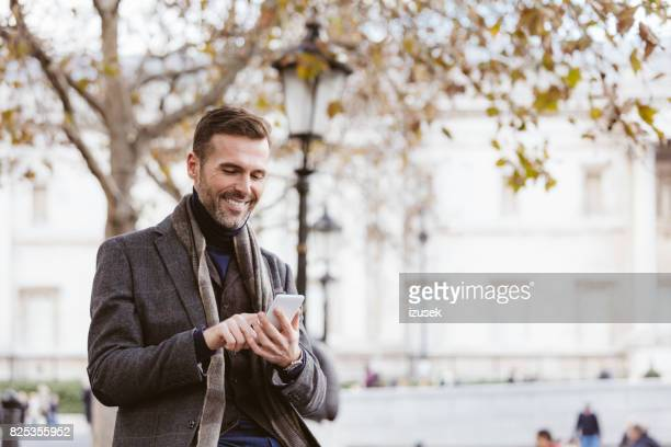 Handsome man using smart phone outdoors in the city