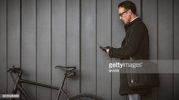 Handsome man, using smartphone beside the bicycle against the grey wall