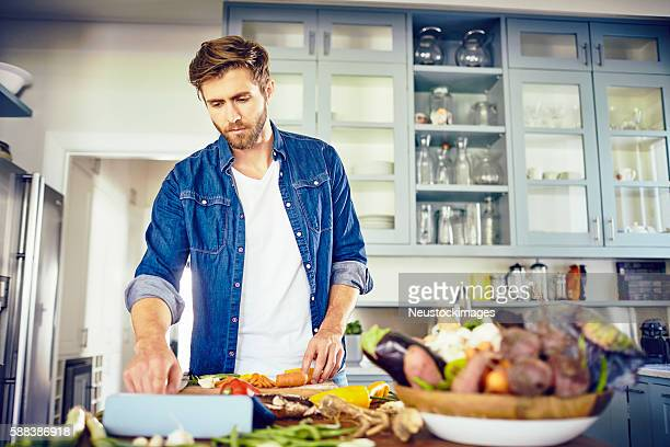 Handsome man using tablet computer while cooking in kitchen