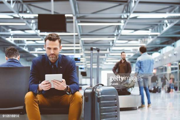 handsome man waiting in airport lounge, using a digital tablet - airport stock pictures, royalty-free photos & images