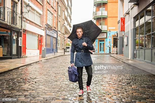 Handsome man walking in the rain