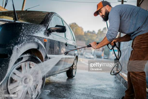 handsome man washing car - auto repair shop exterior stock pictures, royalty-free photos & images
