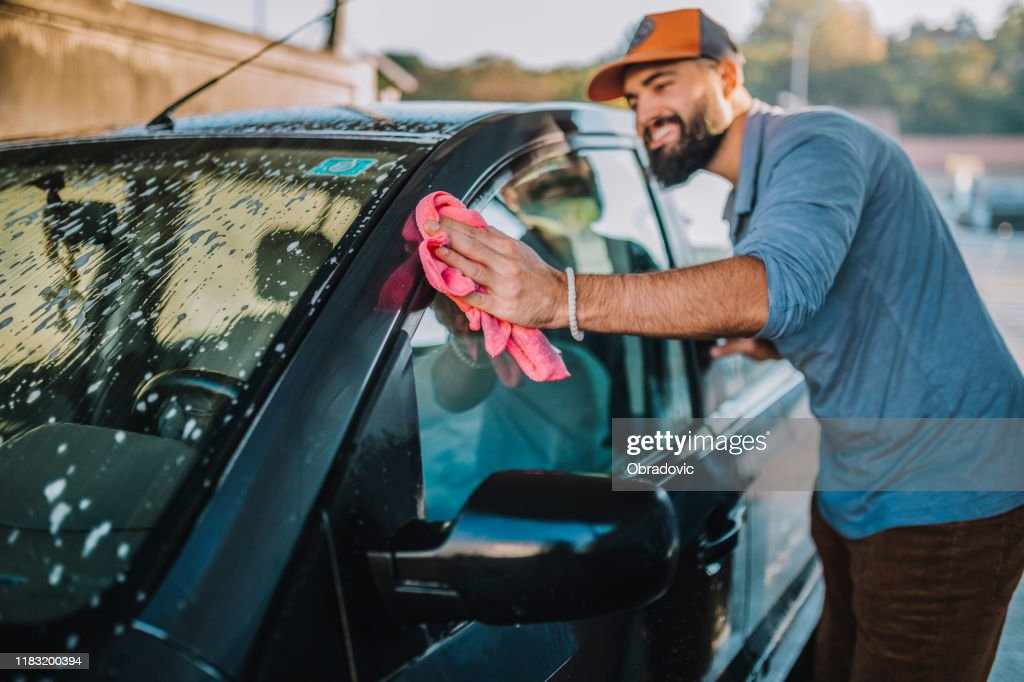Handsome man washing car : Stock Photo