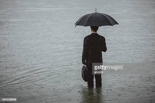Handsome man wearing suit and holding umbrella during the rain