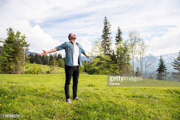 handsome man with arms wide open - vorarlberg stock photos and pictures