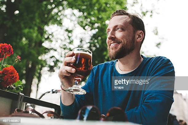 Handsome man with beard drinking bear at a outdoor serving