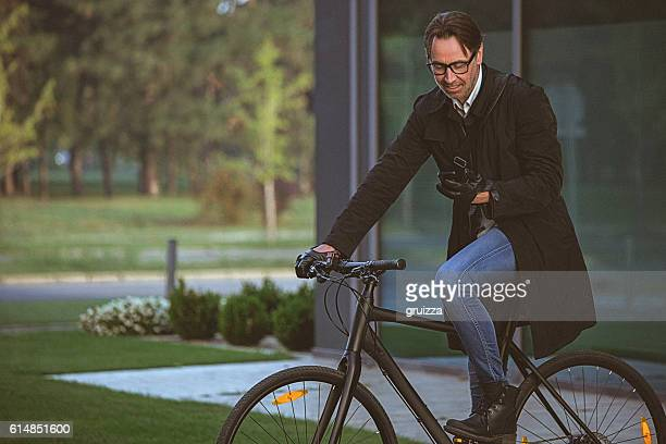 Handsome man with bicycle using smartphone beside the modern building