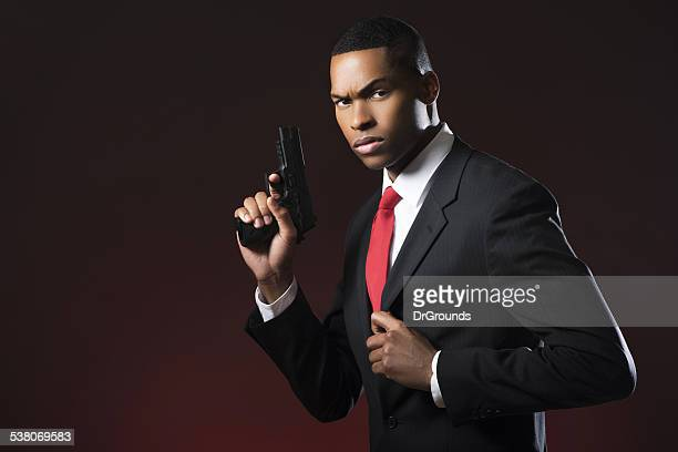 Handsome man with gun in suit portrait