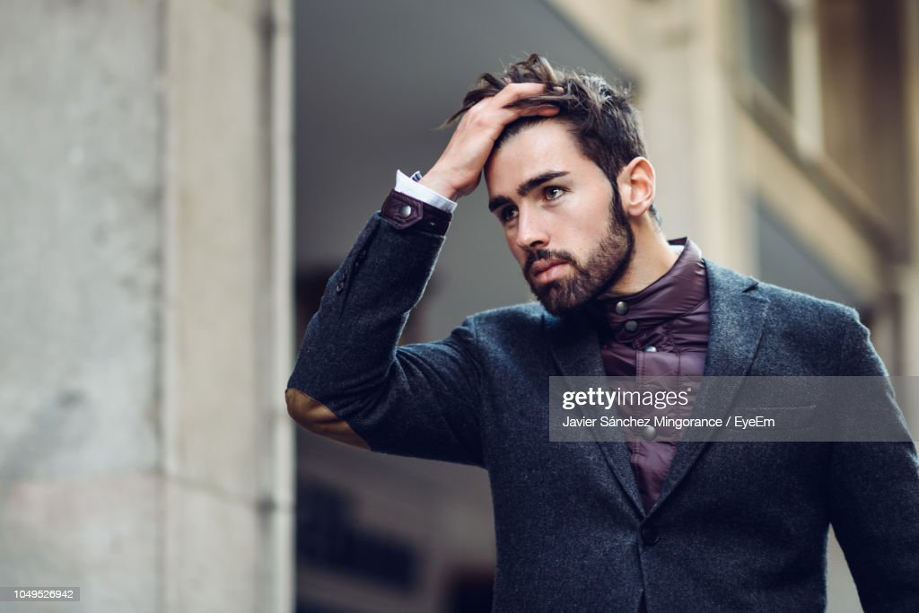 Handsome Man With Hand In Hair Standing By Wall : Stock Photo