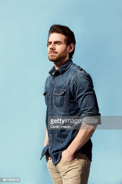 Handsome man with hands in pockets standing against blue background