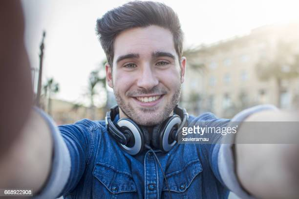 Handsome man with headphones smiling outdoors