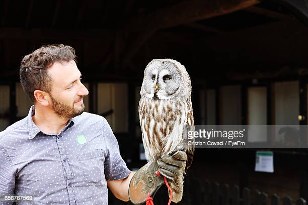 Handsome Man With Owl Perching On Hand