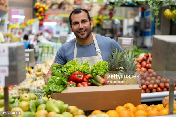 handsome man working at a farmer's market holding an order for customer in a cardboard box looking at camera smiling - bancarella foto e immagini stock