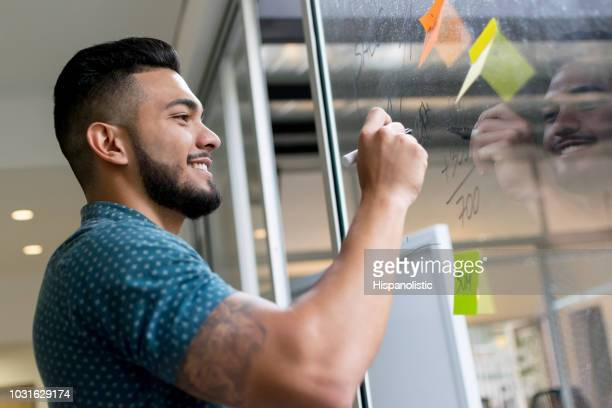 handsome man writing the profits of the company on the window smiling - hispanolistic stock photos and pictures