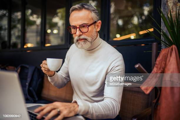 handsome mature adult using laptop. - bar drink establishment stock photos and pictures