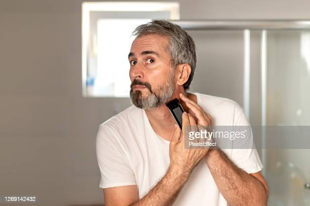 handsome mature bearded man trimming his beard - shaved stock pictures, royalty-free photos & images