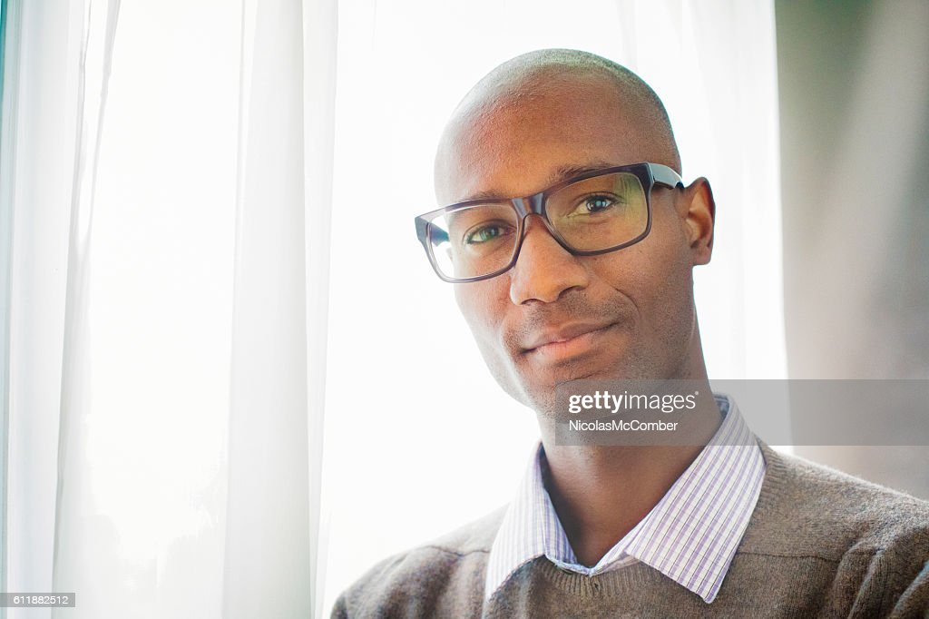 Handsome mature black male bald intellectual portrait by window : Stock Photo