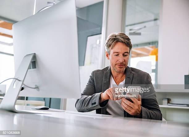 笑顔のハンサムなマチュアダブルエグゼクティブテキストに彼のスマートフォン