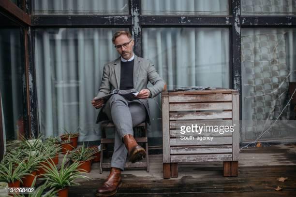 hübsches reifes gentleman, der ein magazin allein liest - einzelner mann über 40 stock-fotos und bilder