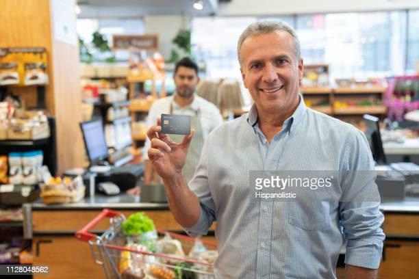 hombre maduro apuesto con una tarjeta de crédito mientras que frente a la cámara sonriendo en el supermercado - charity benefit fotografías e imágenes de stock