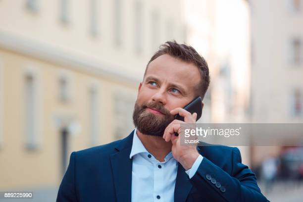 handsome mature man talking on phone outdoors in city - izusek stock pictures, royalty-free photos & images