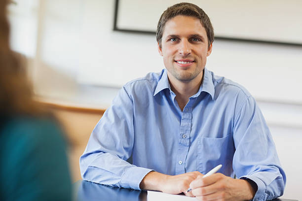 Handsome mature student sitting in classroom