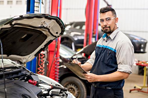 Handsome mechanic job in uniform working on car 998670744